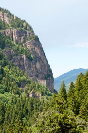look at the edge of the mountain, by the treeline, for the monastery clinging to the cliff